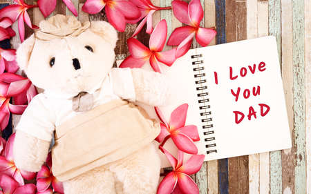 Fathers day greeting card concepts with I love you Dad text and cute Teddy bear doll. Top view on wooden background.