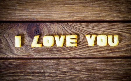 I love you. Text from the salty crackers as printed English letters that lie on a wooden background. Top view. Stock Photo