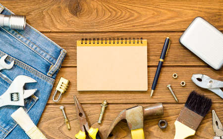 Jeans and many handy tools, blank space notebook on wooden background top view with copy space for text