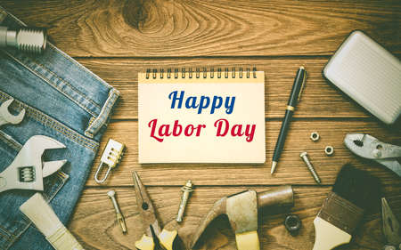 Labor day background concept - Jeans, many handy tools, notebook with happy labor day text on wooden background top view Foto de archivo