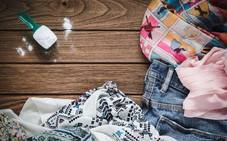messy clothes: Pile of clothes with detergent and washing powder, top view Stock Photo