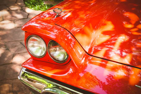 shiny car: Close-up of headlights of red vintage car