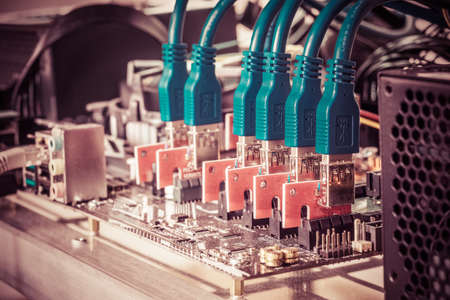 Cryptocurrency background (mining rig), Close up of PCIE riser card plug to motherboard for mining rig machine to mine for digital cryptocurrency such as bitcoin, ethereum and other altcoins.