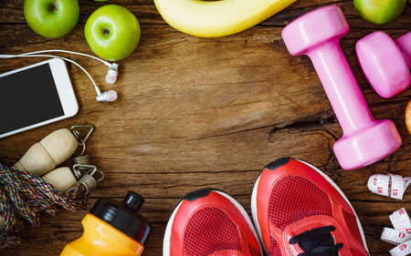 Fitness, healthy and active lifestyles Concept, dumbbells, sport shoes, bottle of waters, smartphone, jump rope and apples on wood background. copy space, top view Stock Photo
