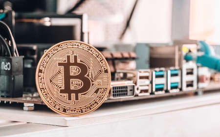 Bitcoin Cryptocurrency background concept - Golden bitcoin with a computer graphic card or GPU rig cryptocurrency mining unit in background Stock Photo