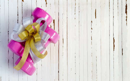 Pink sport dumbbells and gift bow on white wooden background, Merry christmas and Happy new year wish sport gifts concept