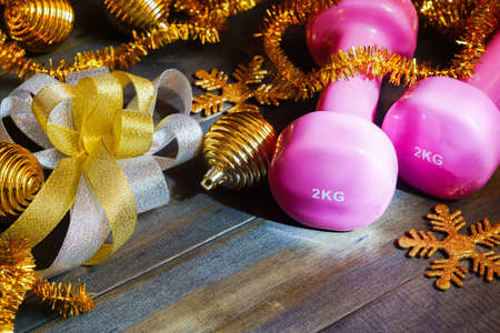 Pink sport dumbbells with Chrismas decoration items and gift bow on wooden background, Merry Christmas and Happy new year wish sport gifts concept