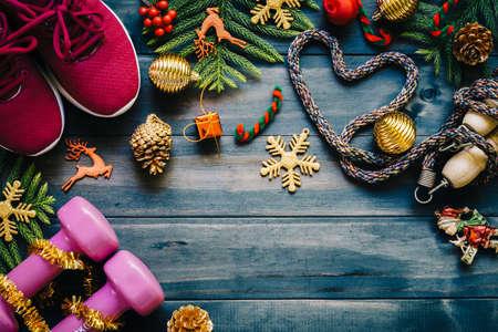 フィットネス、健康でアクティブなライフ スタイル コンセプト、ダンベル、スポーツ シューズ、スキップ ロープや木材の背景にクリスマスの装飾項目をハートで縄跳びが大好きです。運動、フィットネスとクリスマスの作業を幸せな新年のコンセプトです。