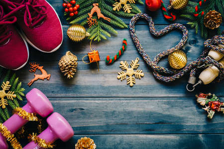 Fitness, healthy and active lifestyles love concept, dumbbells, sport shoes, skipping rope or jump rope in heart shape with Christmas decoration items on wood background. Exercise, Fitness and Working Out Merry Christmas and Happy new year concept.