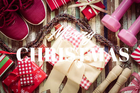 Flat lay of Merry Christmas and Happy new year and any holidy present boxes for healthy and active lifestyle concepts. Composition with dumbbells, sport shoes, skipping rope and red gift boxes with bow on wood background.
