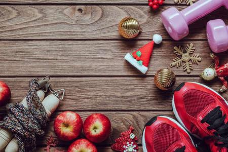 Eignung, gesunde und aktive Lebensstile lieben Konzept, Dummköpfe, Sportschuhe, Springseil oder Seilspringen und Äpfel mit Weihnachtsdekorationseinzelteilen auf hölzernem Hintergrund. Übung, Eignung und Ausarbeiten des Konzeptes der frohen Weihnachten und des guten Rutsch ins Neue Jahr.