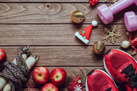 Fitness, healthy and active lifestyles love concept, dumbbells, sport shoes, skipping rope or jump rope and apples with Christmas decoration items on wood background. Exercise, Fitness and Working Out Merry Christmas and Happy new year concept.