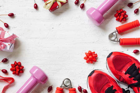 Flat lay of Merry Christmas and Happy new year and any holidy present boxes for healthy and active lifestyle concepts. Composition with dumbbells, sport shoes and red gift boxes with bow on wood background.