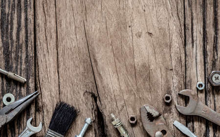 Variety Handy Tools on grunge wooden background. Top view close up of wrenches, Pliers, screwdriver, nuts and bolts on wood background with copy space for your text. Workers, Labors day background.