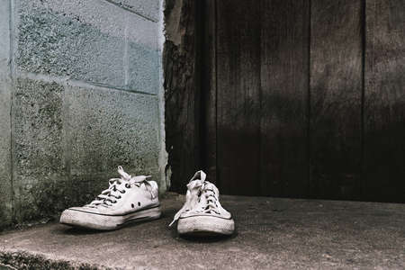 White dirty pair of sneakers with grunge old wood wall  background in old town Stock Photo