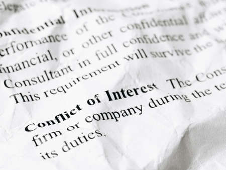 Still life close up shot of Conflict of Interest word message on crumpled and wrinkled contract paper