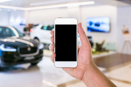 man hand using mobile smart phone with blank screen in a blurred background of car showroom