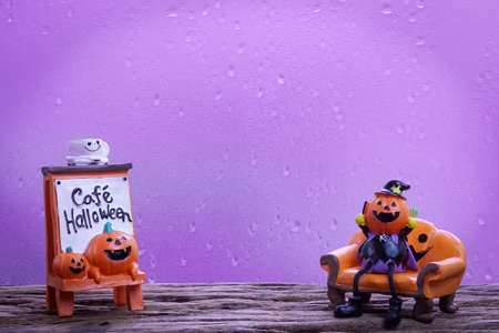 Halloween festival Head Doll Pumpkins  haunted spooky with coffee cup on top and text cafe halloween decoration on wood background. Blank space available for your text. Stock Photo