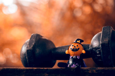 Halloween festival Close up of Halloween head Pumpkins doll and the black iron dumbbell. Fitness, healthy active lifestyle on Halloweeen day concept. Stockfoto