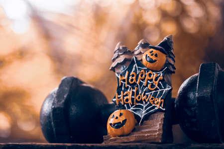 Halloween-Festival Nahaufnahme der Halloween-Kopf-Kürbis-Puppe und der schwarzen Eisenhantel. Fitness, gesunder aktiver Lebensstil auf Halloween-Tageskonzept.