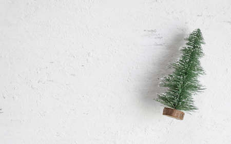 Flat lay top view of mini christmas tree wood on rustic white wooden table. Winter holiday seasonal greeting card. Blank space for your text or design.