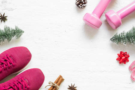 Flat lay of Merry Christmas and Happy new year for healthy and active lifestyle concepts. Composition with dumbbells, sport shoes and Christmast decoration on grunge white wood background. Stok Fotoğraf