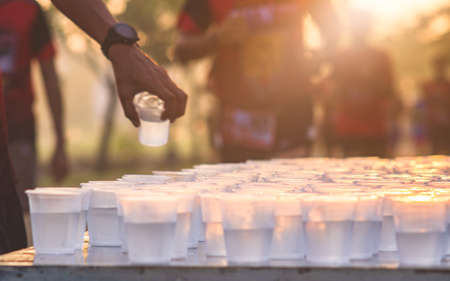 Marathon Runner take a water at a service point in a marathon race with sunrise, selective focus, shallow DoF