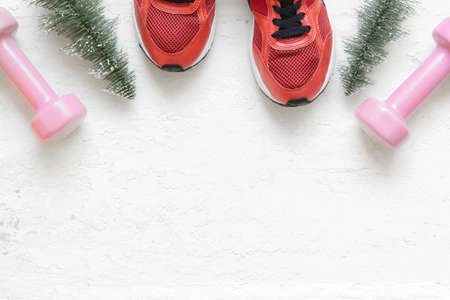 Christmas healthy acive lifestyle flat lay composition with sneakers, dumbbells, christmas tree on grunge white wood  background. Merry Christmas and Happy new year background special for healthy life