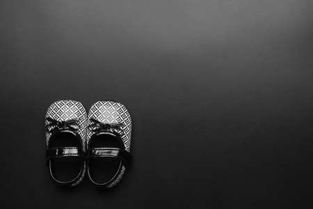 Black and White  children baby shoes on black background