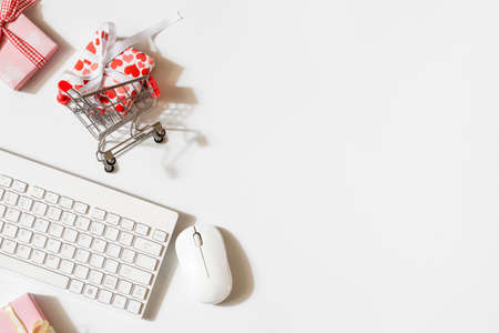Overhead shot of wireless keyboard and mouse, gifts box with shopping cart. Flat lay top view office working space for Valentines' day and women's day shopping online concept. Stock Photo