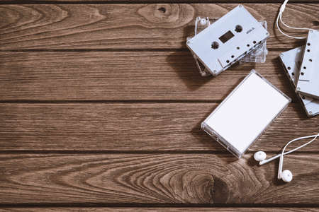 Overhead shot of retro old audio cassette tape with earphone on vintage retro wooden background, flat lay top view with copy space. Stock Photo