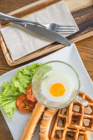 Homemade delicious american breakfast with soft-boiled egg, waffles, sausage, tomato, lettuce on white plate on wood table, top view. Stock Photo