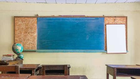 Wnętrze rocznika retro klasie z pustą tablicą dla Twojej przestrzeni kopii. Koncepcja edukacji i szkoły. Pusta niebieska tablica przed klasą szkolną z drewnianymi biurkami i krzesłami dla uczniów