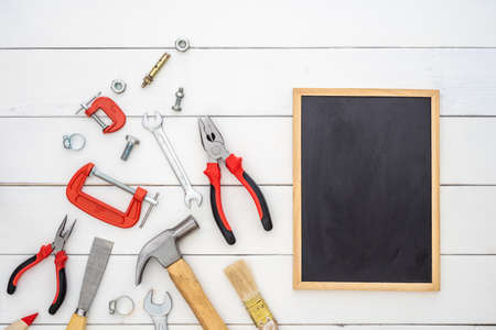 Flat lay of blank space blackboard with construction handy tools over wooden background. Top view with copy space for your advertising text.