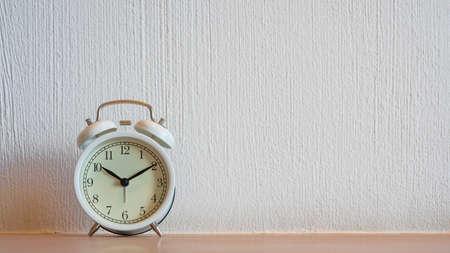 Biały rocznika budzik wyświetlający 10:10 lub pm na drewnianym stole i tle białej ściany.