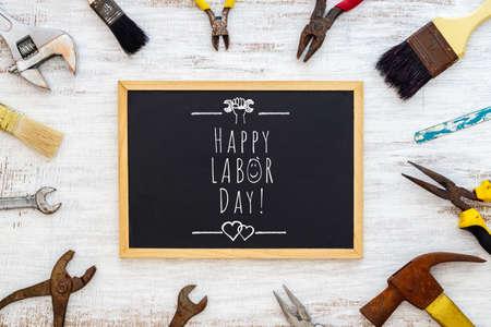 劳动节快乐的背景概念。生锈的旧手工具用黑板和文字书写德赢体育劳动节快乐!