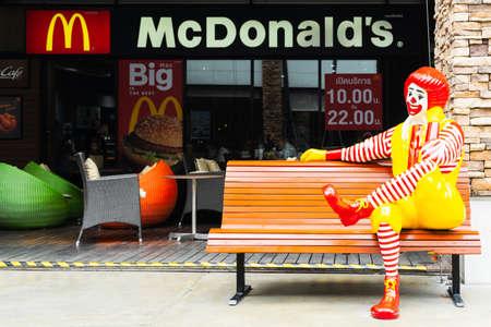 BANGKOK, THAILAND - 2019 JUNE 16: Ronald McDonald character sitting on bench, in front of McDonalds restaurant. Ronald McDonald is a clown character used as the primary mascot of the McDonald's restaurant chain.