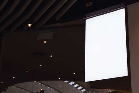 Blank white screen vertical signage mockup hanging on ceiling. Signboard for advertisement design in a shopping center, gallery.