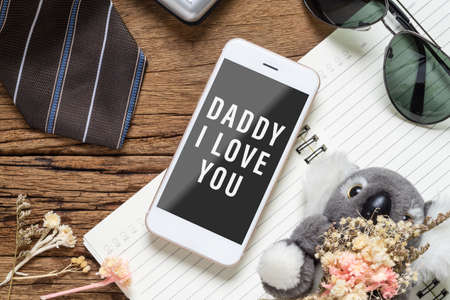 Fathers day background concept. Mock up mobile phone for your artwork with Fathers accessories items and daughters toy on wood with Dady I love you messages on smartphone.