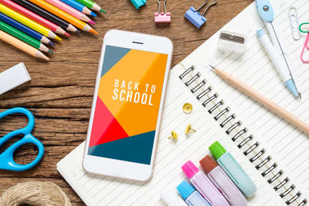 Back to school background concept. Mock up mobile phone for your artwork with School stationary items on rusty wooed background, top view flat lay background. Reklamní fotografie