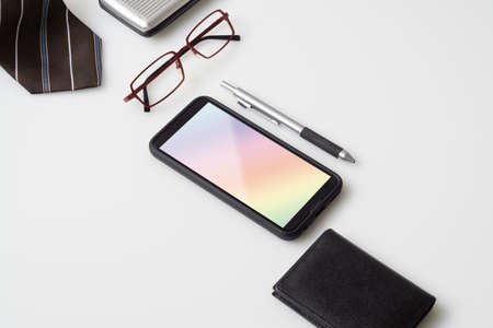 Mobile phone mockup with gentlemens accessories, glasses, wallet, pen and necktie with copy space on white color background. Top view Office desktop with accessories, Desktop with business objects.