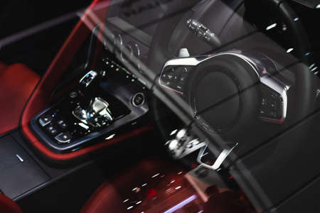 The steering wheel and interior of luxury sport car. View through the  windshield windows of steering wheel and dashboard in interior of the sports car.
