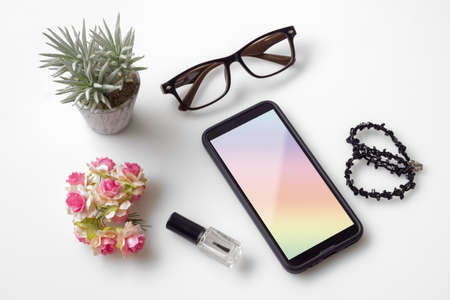 Top view feminine mobile phone mockup. Overhead shot of womans desktop workspace with smartphone mockup, cosmetic, glasses, womans accessories on white background Reklamní fotografie