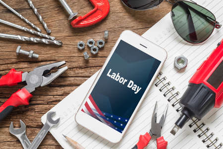 Table top view of decoration the sign of USA labor day background concept. Flat lay mock up Smart Phone With Labor Day USA Holiday and essential construction tools worker on grunge wood background.