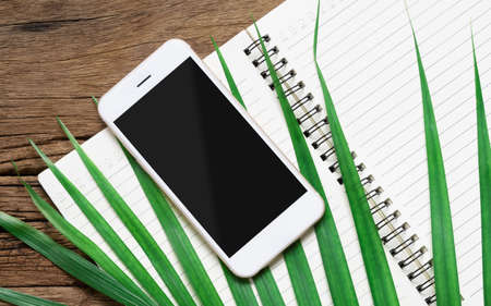 White smartphone with black blank mockup screen with green palm leaves and open notebook on the grunge wood desk table. Top view with copy space, mock up flat lay.