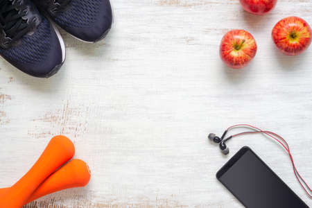 Top view of Active healthy fitness and workout lifestyle background concept, sport shotes, dumbbells, smartphone and apples on grunge white wood  background with copy space. Flat lay. Reklamní fotografie