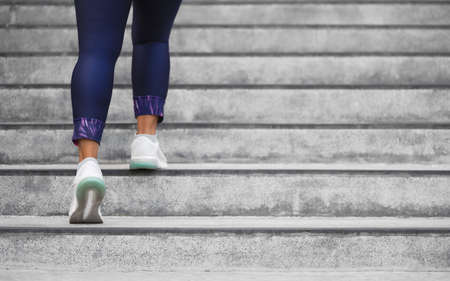 Female runner athlete doing a stairs climbing. Running woman doing run up steps on staircase in urban city. Doing cardio sport workout. Exercise outside in summer. Activewear leggings and shoes. Reklamní fotografie