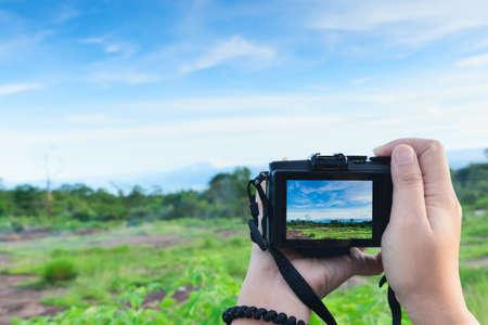 Traveller make photo  using mirrorless camera in hand, travel blogger, Close up of womens hands holding mirrorless camera taking picture
