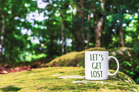 Inspirational Travel Quote - Lets Get Lost on the white mug. Close up white mug for your mock-up in the tropical forest.