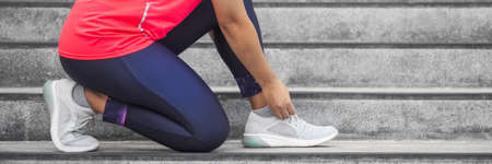 Woman tying shoelace on running shoes before practice. Runner getting ready for training. Sport active lifestyle concept.  Outdoor workout concept for web banner, website page etc. Wide banner panorama living healthy lifestyle Reklamní fotografie